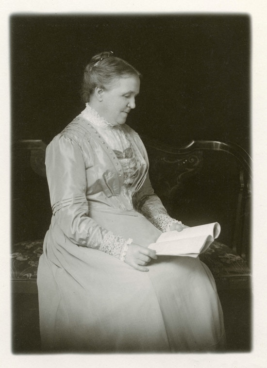 Srah Fuller seated, reading.