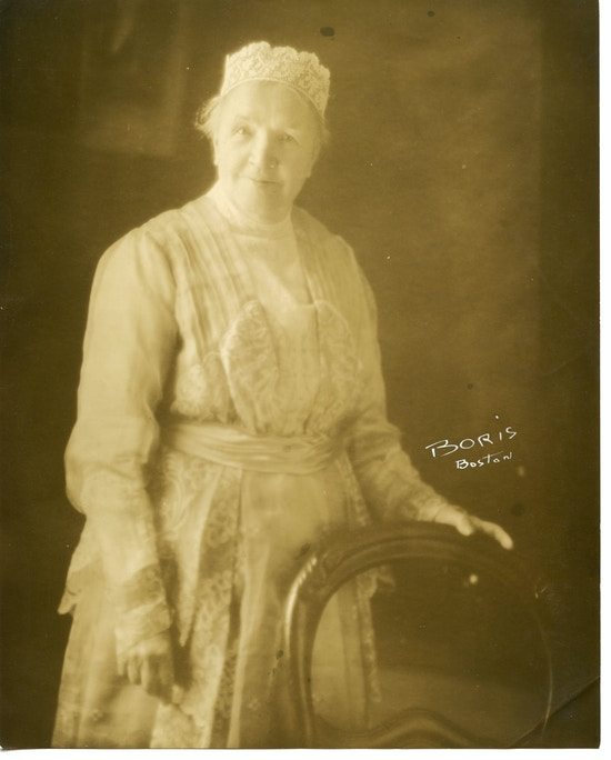 Sarah Fuller standing, with hand on chair.