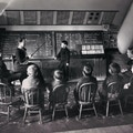 Photograph of Sarah Fuller's class with seated students facing chalkboard, away from camera. One student is standing at the board with Fuller instructing.