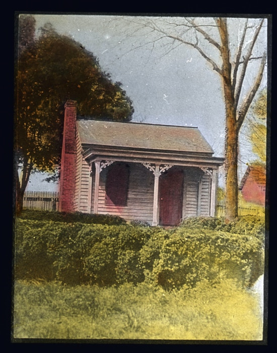 A small cottage with shrubs in foreground near Helen Keller's childhood home in Tuscumbia, Alabama.