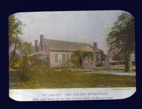 "Helen Keller's childhood home, Ivy Green, in Tuscumbia, Alabama. The photograph caption reads, ""Ivy Green, The Keller Homestead. The small house on the right is where Helen Keller was born""."