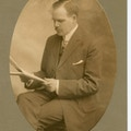 John Wright seated, looking down and left at possibly a manuscript or newspaper.