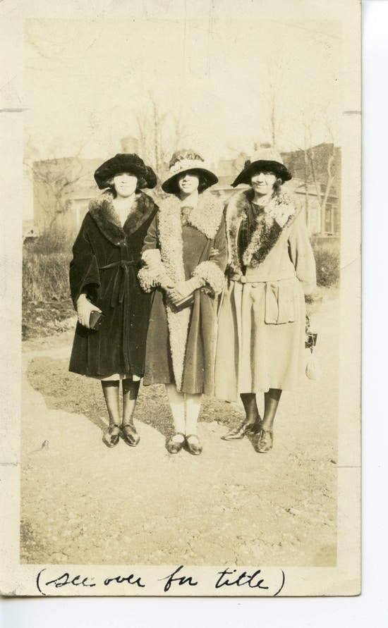 Three women, probably either teachers or alumni, standing arm in arm.