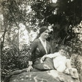 Helen Keller and young Jack Wright under a large tree in Mr. Wright's garden.