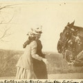 Helen Keller and Anne Sullivan (both left) stand together facing horses positioned right in Boston suburbs.