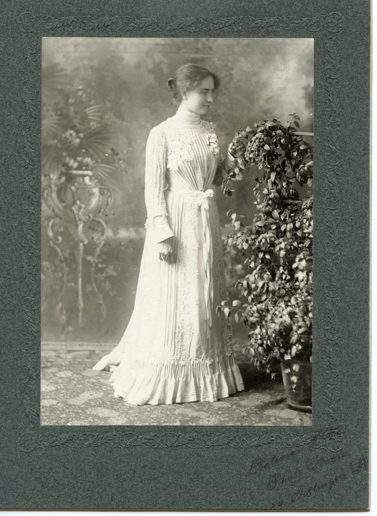 Helen Keller standing, facing right, wearing long sleeve, floor length, white gown with waist sash, facing plant.