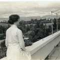 Helen Keller in a long sleeved, light colored dress standing outside, overlooking an expansive view of trees and hills in background.