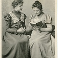 Anne Sullivan (right) finger spelling a book with Helen Keller (left), both seated.
