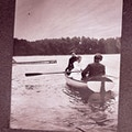 Helen Keller rowing in rowboat with one passenger each at the head and tail of the boat.