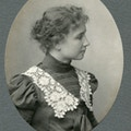 Helen Keller wearing lace collared dress with hair in a bun facing right in a head and shoulders portrait.