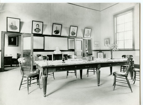 A laboratory room at the Volta Bureau with pictures, a large table, and chairs surrounding the table.