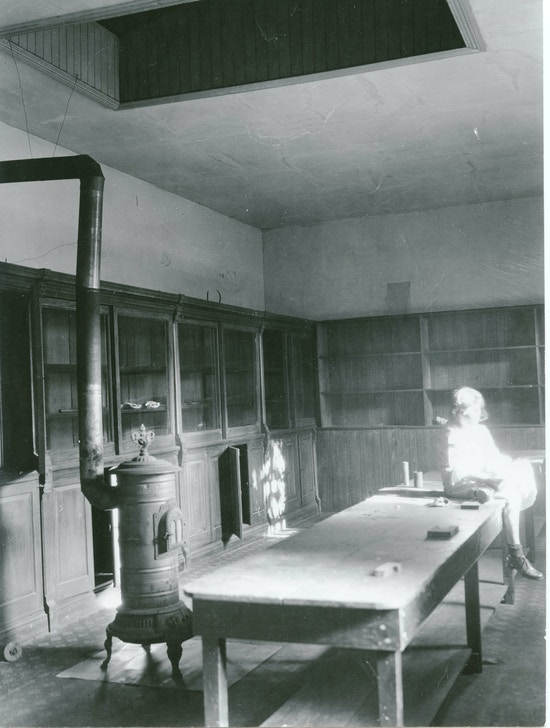 Interior of the coach-house of the Alexander Melville Bell's home across the street from the Volta Bureau. Coal stove near a table.