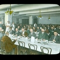 Large dining hall, men serving food to men with suit jackets at long tables, tablecloths set.