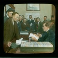 Lantern slide of men waiting in line to speak to a salvation army worker, probably in NY.