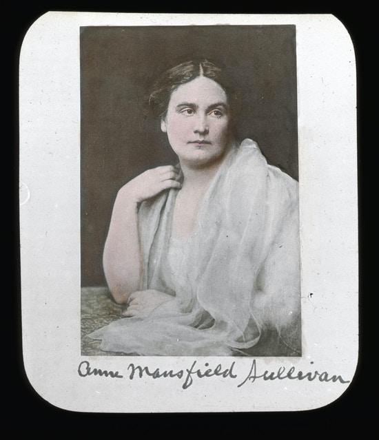 Portrait of Anne Sullivan, seated, wearing all white, head facing right with body turned left.