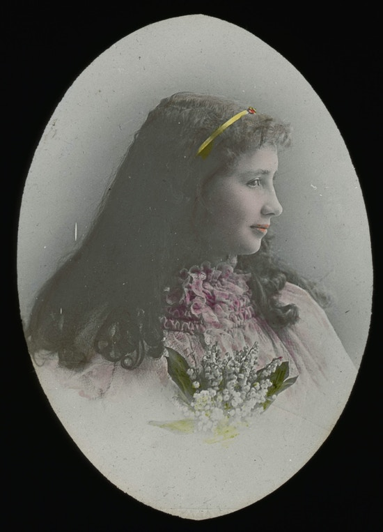 Helen Keller wearing dress with lace at collar and holding flowers side view facing right for a colored, head and shoulders portrait.