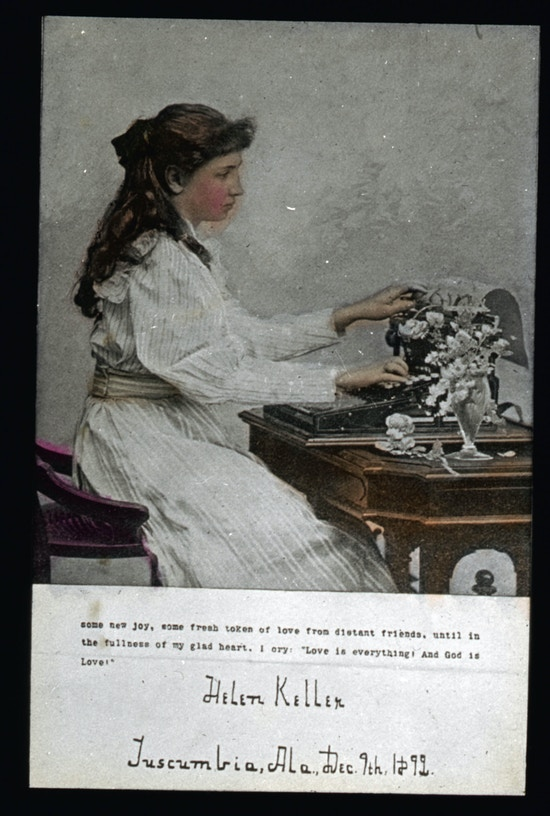 Young Helen Keller seated facing right, wearing a long sleeved dress at a table typing on a typewriter or braille writer.  In color.
