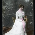 Helen Keller seated wearing a formal white gown with pink ribbon around the waist and holding flowers.