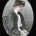 Helen Keller in her graduation gown, seated, facing right, colored.