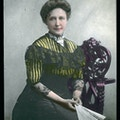 Kate Adams Keller facing right with bun in hair in a color lantern portrait.