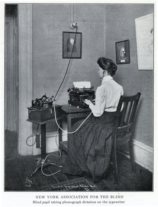 Woman sitting at a typewriter taking dictation.