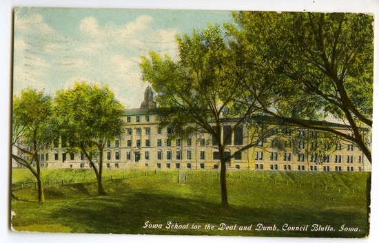 Iowa School For The Deaf And Dumb. A large building with grass and trees. A large building with dome, pillars, and trees.