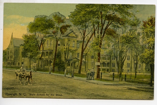 State School for the Deaf, Raleigh, North Carolina.  Ornate building with many trees, a horse and buggy passing.