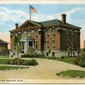 Blind Institute, Saginaw, Michigan. A two-story brick building with an American flag on top.