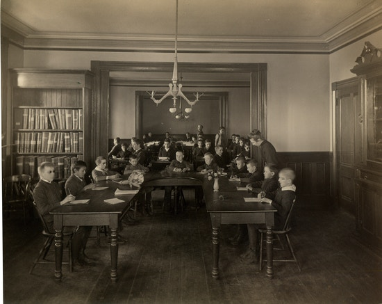 Classroom filled with boys at the Perkins Institution and Massachusetts School for the Blind in South Boston. They are seated around a large U-shaped wooden table with an assortment of plants, pine cones, and flowers. Each boy has a writing tablet and writing instrument.