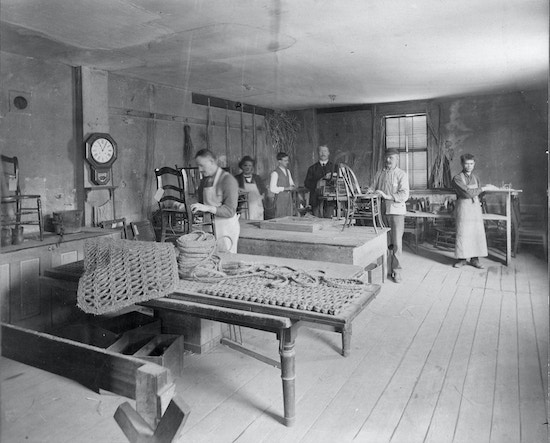 Workshop for the Blind, Perkins Institution for the Blind, Fourth Street, South Boston, Mass. In front are two thick door mats and a spool of the thick cord used to make them. Six men stand in the back of the room at work stations. Some work on chair caning. One of the faces has been enhanced with pen for publication purposes.