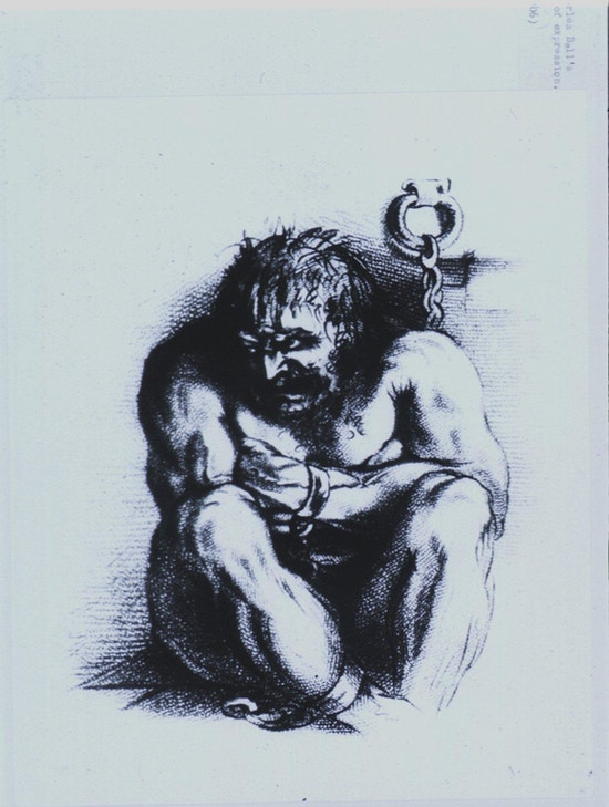 A powerfully built, angry looking man is sitting on the floor, arms folded and knees are drawn up close, his head is turned to the left; his wrists and ankles are in irons which are chained to the wall.