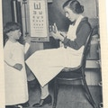 A boy and a woman with eye chart.