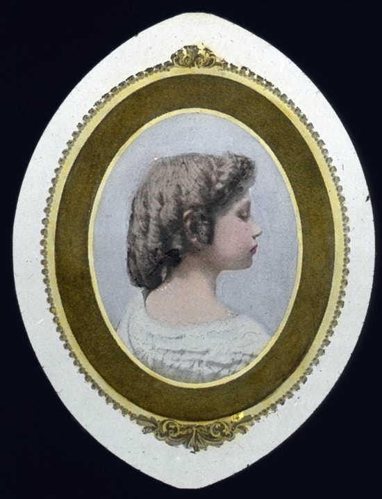 Color portrait of child Helen Keller with her hair in ringlets facing profile side right.