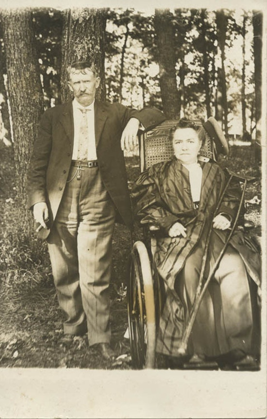Woman sitting in wheelchair and holding crutch. Man stands next her holding cigar.