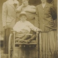 Three women with little boy in a wheelchair.