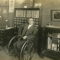 Man using wheelchair in an office, another man at a desk.