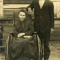 Elderly Man And Woman With Wheelchair,  Woman dressed in long dress.
