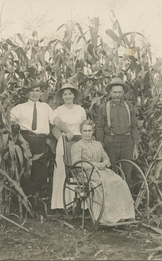 Two men and one woman standing behind elderly woman in a wheelchair, tall corn in background.