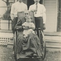 Two Men, Baby, And Elderly Woman In Wheelchair.  Next to building with porch.
