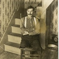 A man, a double-leg amputee, sits in chair, next to stairs.
