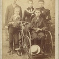 Portrait of family. One boy uses a wheelchair.  Another poses with his bicycle.