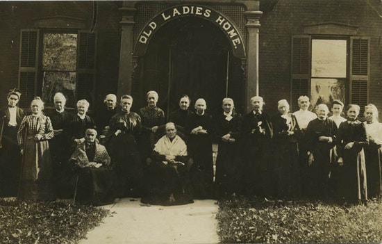 "A group of two dozen elderly women under a sign saying ""Old Ladies Homes."""