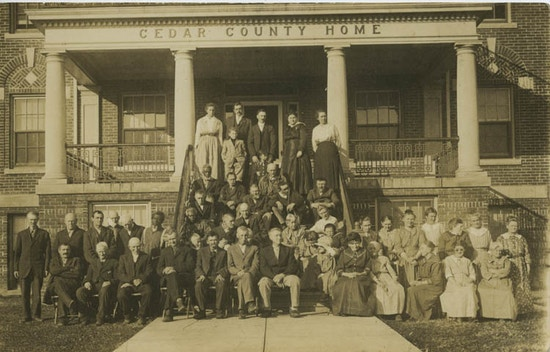 Group photo of men and women on steps of building.