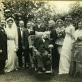 Family gather on a wedding day. Man at center in a wheelchair.