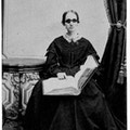 Bridgman, seated facing camera, holding book, dark dress with lace collar, dark glasses.