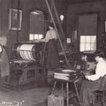 One man with apron, two women in light blouses and dark skirts, printing equipment.