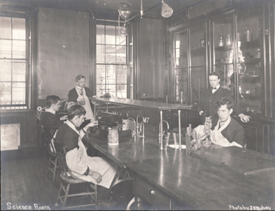 male students seated around table with science experiments, holding chemistry beakers.