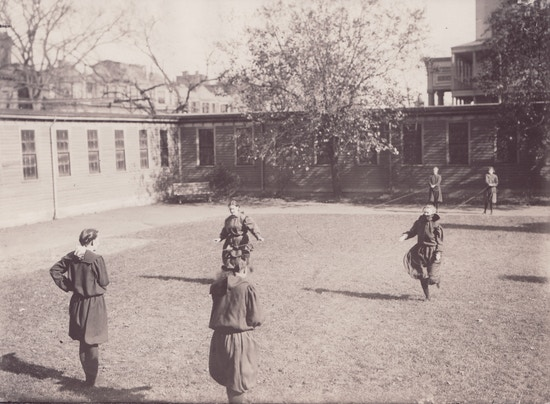 Children playing potato sack race with guiding cables, background shows Perkins entryway portico.