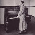 Man in white lab coat stands in profile at piano, working with tuning instruments.