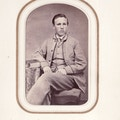 Edward Howarth, seated portrait, light suit, legs crossed.